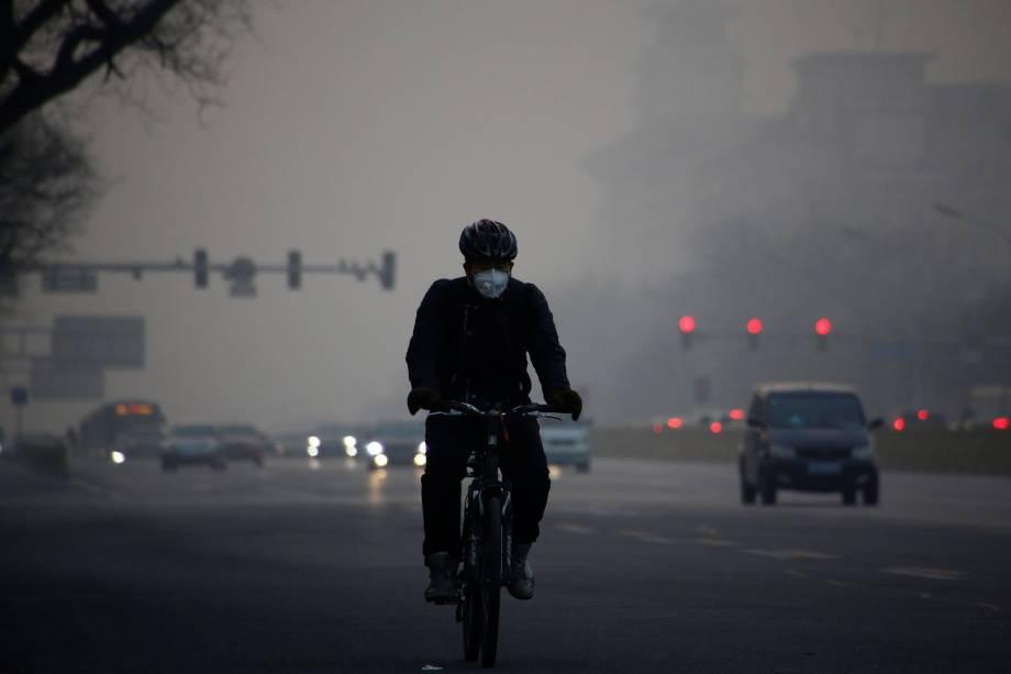 Ciclista usa uma máscara enquanto pedala em uma avenida em meio a uma densa camada de poluição em Pequim, na China - 03/01/2017