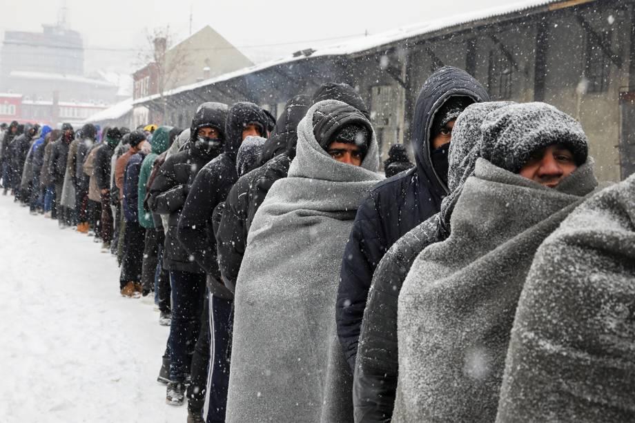 Migrantes aguardam em fila para receber alimentos, durante nevasca em Belgrado, na Sérvia - 11/01/2017