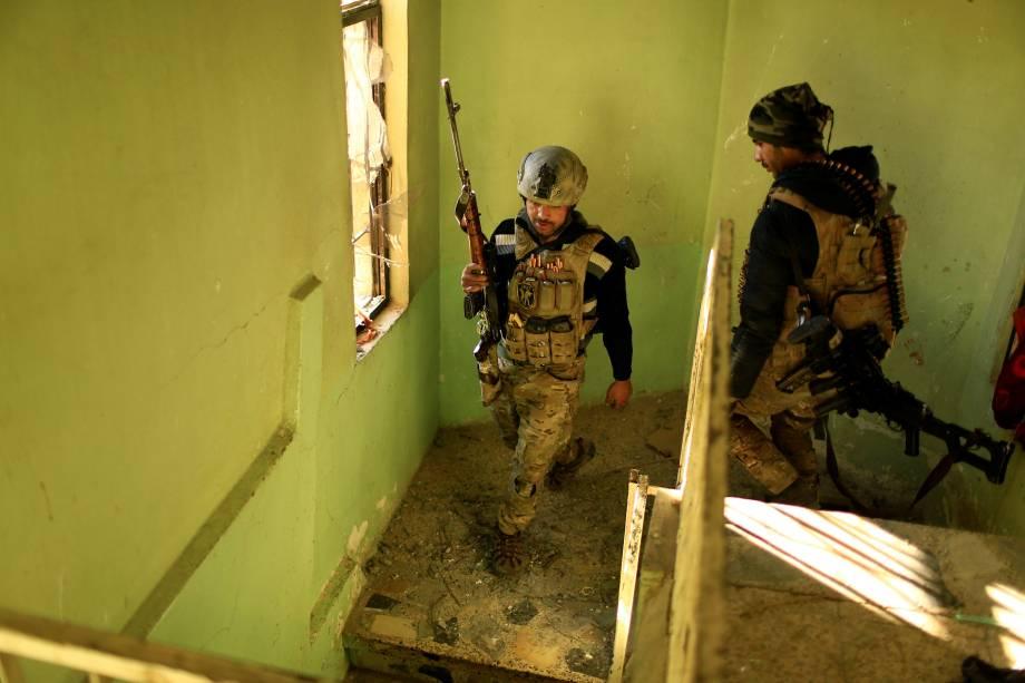 Integrantes das forças iraquianas caminham em um prédio durante a batalha contra militantes islâmicos no distrito de Mithaq, no leste de Mosul, no Iraque