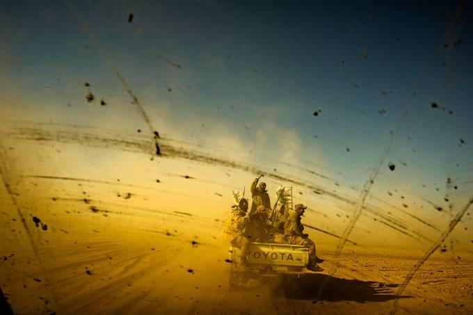 RUMO AO FRONT –  Membros das milícias xiitas ao cruzar o deserto para interceptar os combatentes do EI que tentam fugir para a Síria