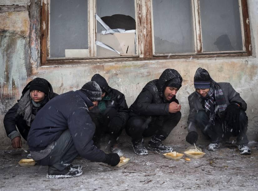 Imigrantes se alimentam do lado de fora de ujm armazém durante nevasca em Belgrado, Sérvia