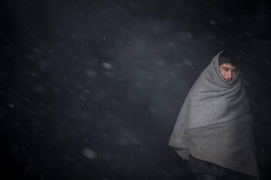 Imigrante se aquece com um cobertor durante forte nevasca em Belgrado, Sérvia