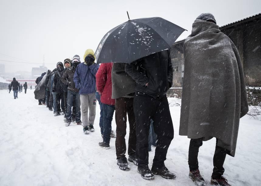 Imigrantes fazem fila em meio a nevasca, para receberem comida, em Belgrado, Sérvia