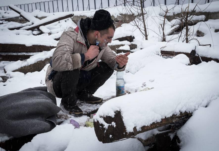Imigrante faz a barba cercado de neve em Belgrado, Sérvia