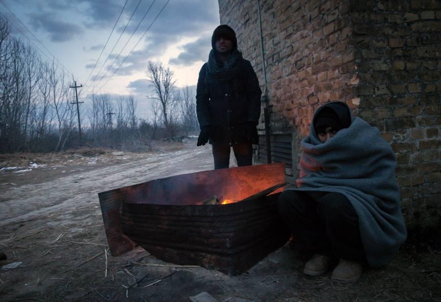 Imigrantes se aquecem em volta de uma fogueira, para se protegerem das temperaturas de menos 20 graus celsius, em Belgrado, Sérvia