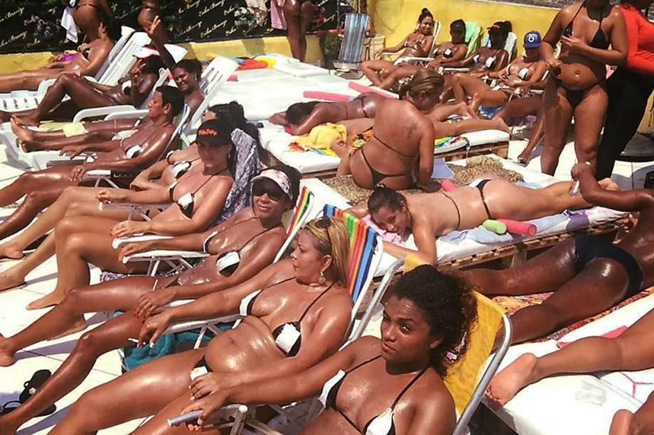 Mulheres tomam sol com fita isolante no ligar do biquíni, na laje de Érika Bronze, no Rio