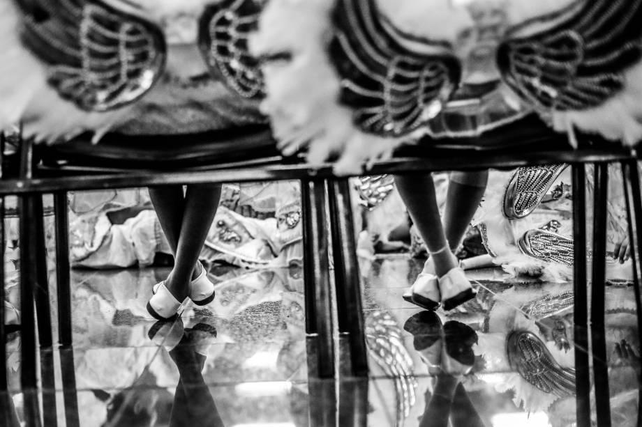 Garotas descansam momentos antes de desfilar no Sambódromo Anhembi, em São Paulo