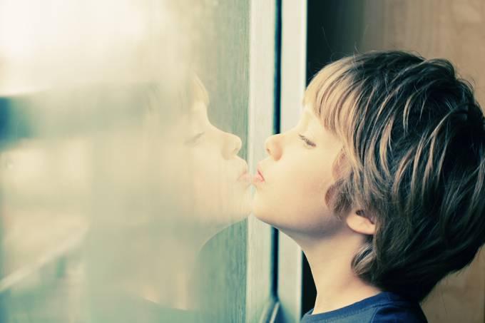 Garoto olhando pela janela