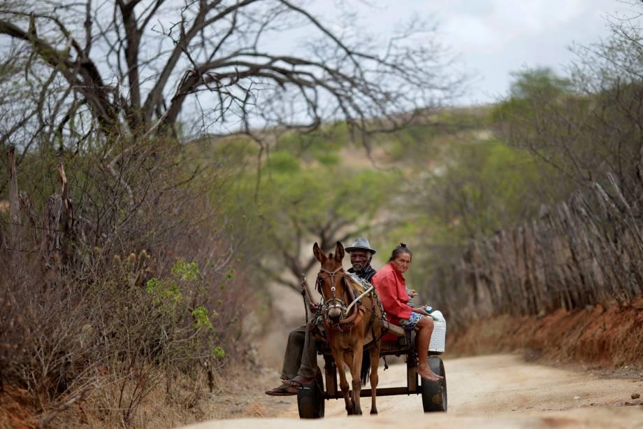 Francisco Barbosa Cruz, 82 anos, e sua esposa Maria de Lourdes, 65, atravessam a paisagem árida sobre uma carroça na cidade de Pombal, Paraíba