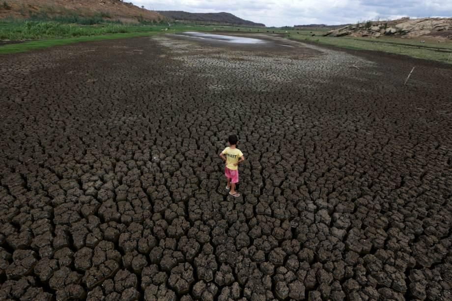 Natan Cabral, 5 anos, caminha sobre o solo rachado do reservatório de Boqueirão, na região metropolitana de Campina Grande, Paraíba