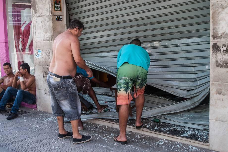 Homens consertam uma porta de loja após ataque de assaltantes em Vila Velha, no Espírito Santo - 06/02/2017