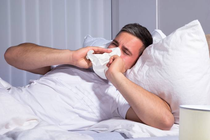 Homem assoando seu nariz