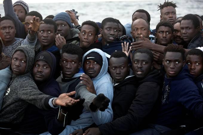 Imigrantes sub-saharianos são vistos a bordo de um barco superlotado, durante uma operação de resgate da ONG espanhola Proactiva Open Arms, no Mar Mediterrâneo, a 21 milhas ao norte da cidade litorânea libanesa de Sabratha
