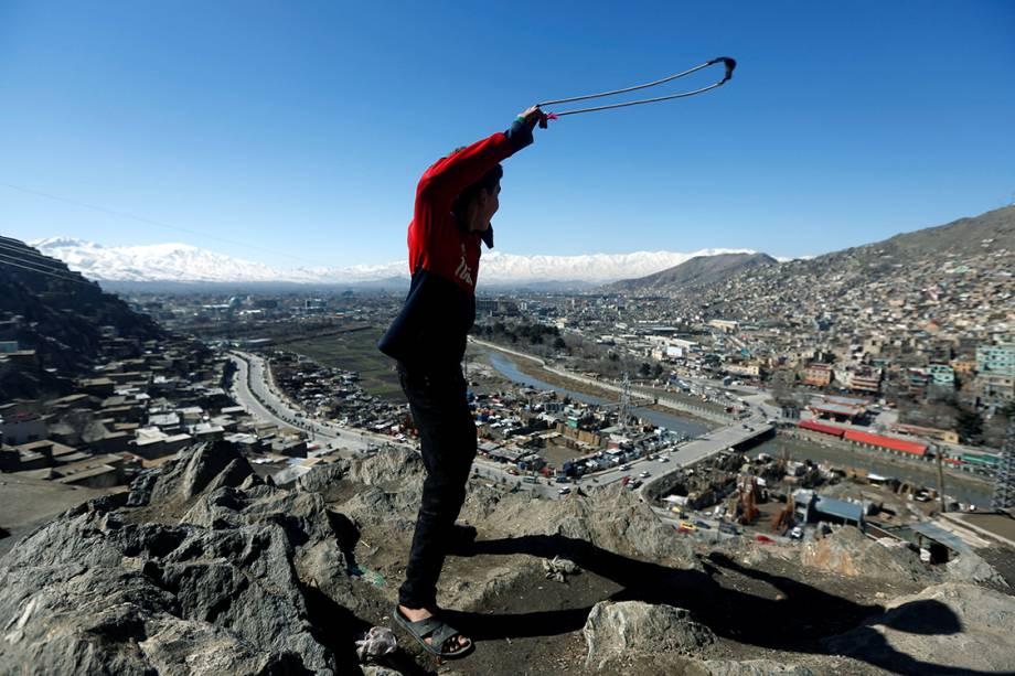 Garoto afegão brinca no topo de uma colina em Cabul - 20/02/2017