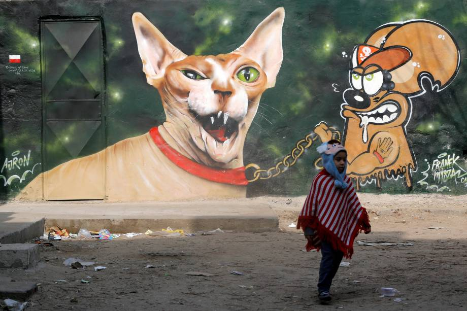 Menina é fotografada em frente a um grafite pintado na parede de uma casa situada em um complexo do século XV construído pelo sultão de Mameluk Al-Ashraf Qaitbey, na cidade do Cairo, no Egito