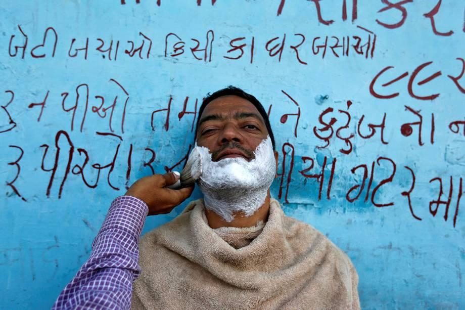 Homem faz a barba em uma estrada na cidade de Ahmedabad, na Índia - 27/02/2017