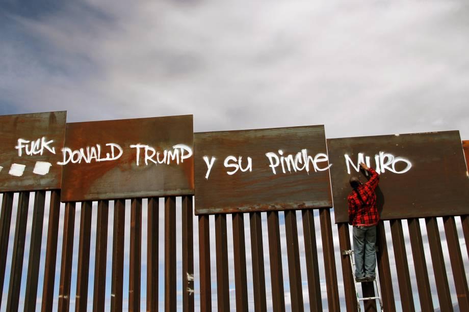 Ativista picha um trecho do muro na fronteira entre Estados Unidos e México durante uma manifestação contra o presidente dos EUA, Donald Trump, em fronteira de Ciudad Juarez, no estado mexicano de Chihuahua - 27/02/2017