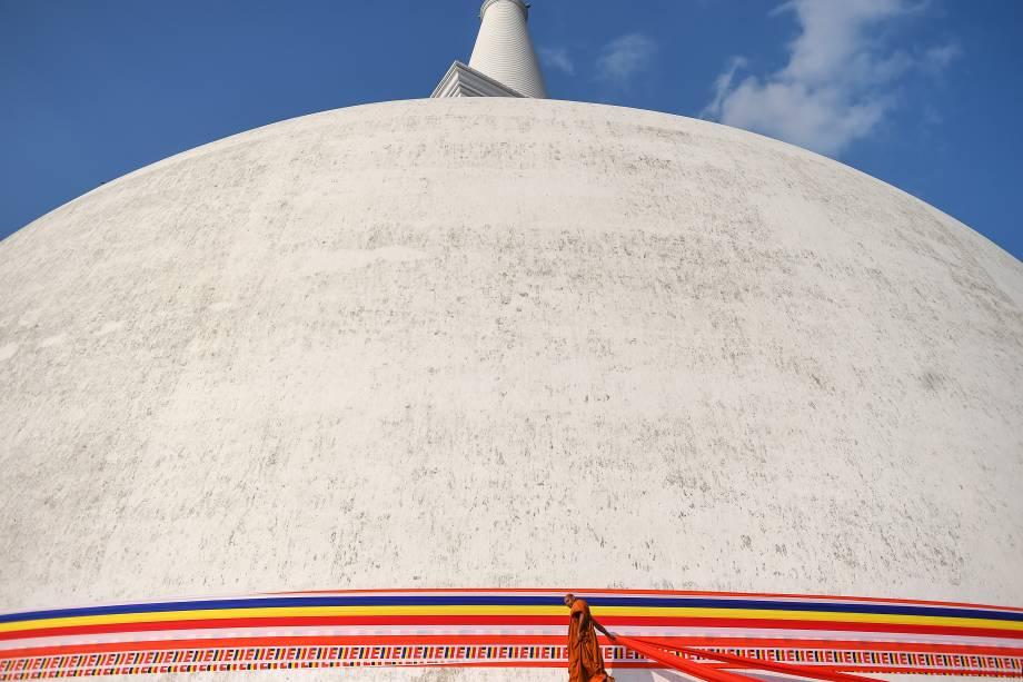 Budista é fotografado em frente ao templo Ruwanwelisaya fazendo uma oferendadurante o Poya, festival religioso da lua cheia, na cidade de Anuradhapura, Sri Lanka - 10/02/2017