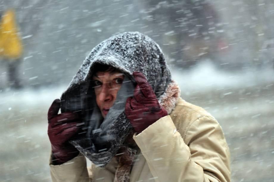 Uma mulher se protege da neve com seu cachecol-09/02/2017