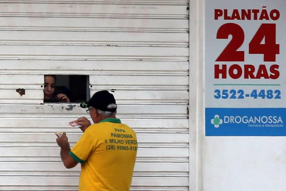 Mulher vende remédios em uma farmácia através de uma janela, em Cachoeira do Itapemirim, Espírito Santo
