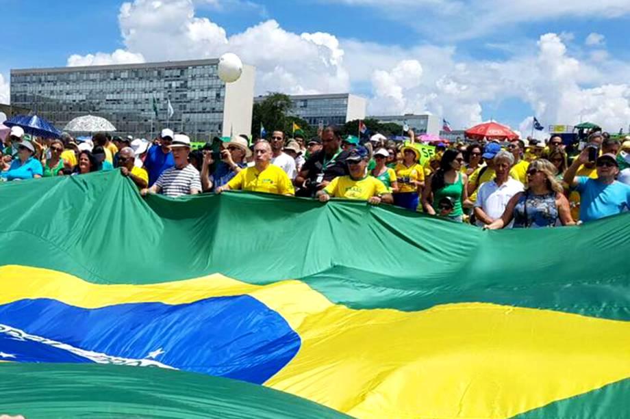 Manifestantes seguram uma bandeira do Brasil durante protesto no Palácio do Planalto em Brasília - 26/03/2017