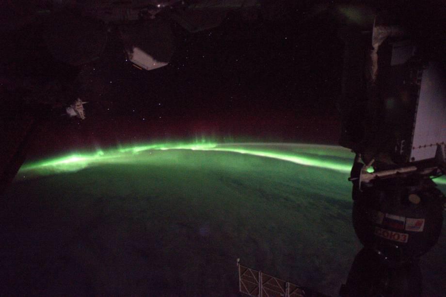 """Imagem de uma aurora boreal cruzando parte do globo terrestre. """"Depois de passar alguns dias sem olhar para fora, fui fotografar a vista da cúpula por cinco minutos depois do almoço. Aqui está o que eu encontrei!"""", diz o astronauta"""