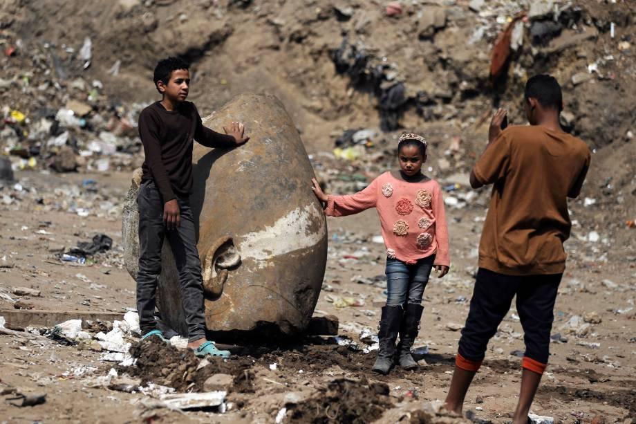 Crianças fazem fotos próximas a cabeça de uma estátua do faraó Ramsés II encontrada por trabalhadores em uma favela no Cairo - 09/03/2017