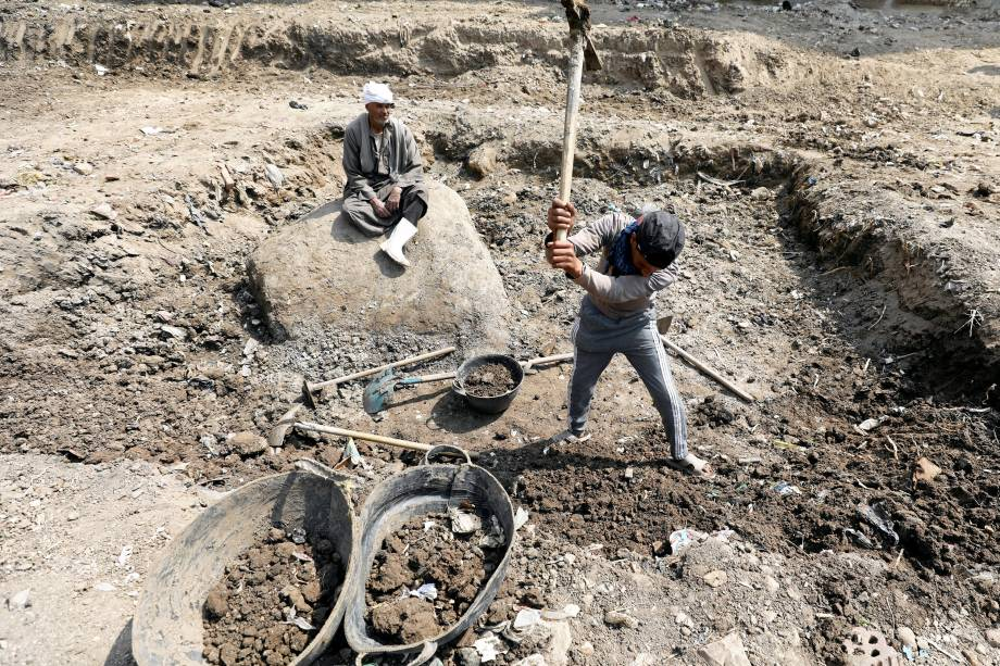 Homens trabalham no local onde uma estátua do faraó Ramsés II foi encontrada em uma favela no Cairo - 09/03/2017