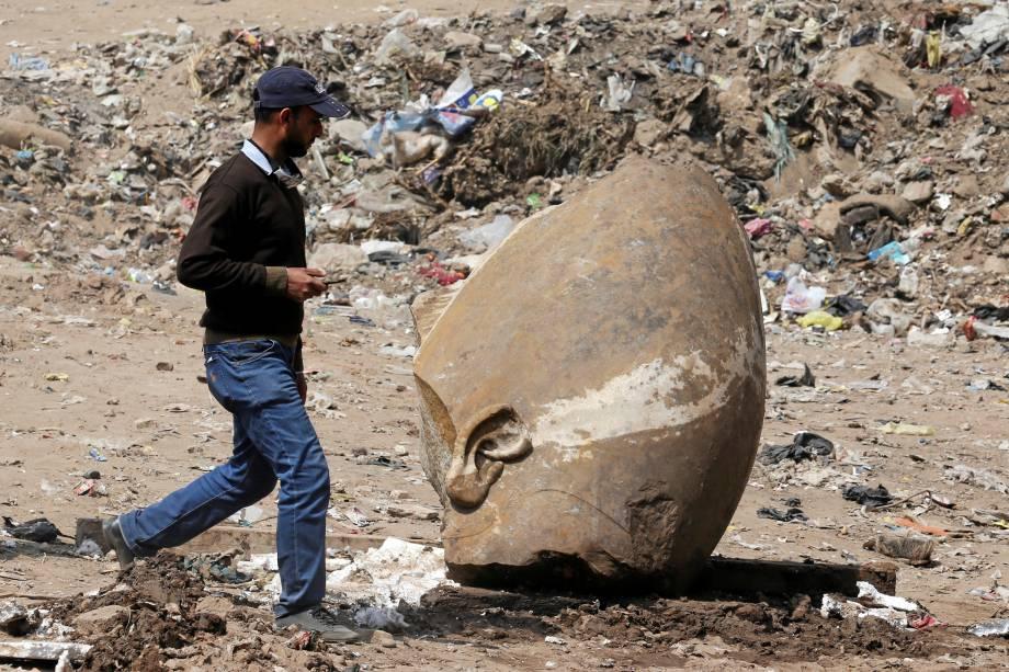 Homem passa pelo que parece ser a cabeça de uma estátua do faraó Ramsés II encontrada por trabalhadores em uma favela no Cairo - 09/03/2017