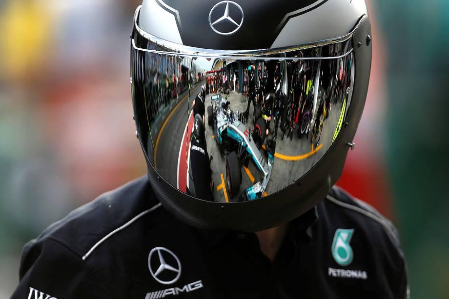O finlandês Valtteri Bottas da Mercedes aparece refletido no capacete de um mecânico durante o treino de sexta-feira (24)