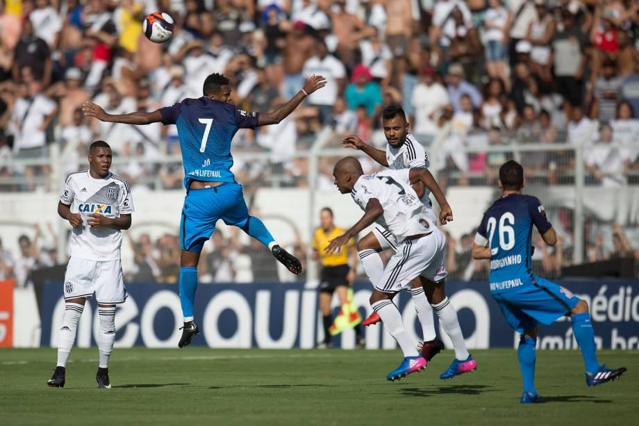 O atacante Jô do Corinthians disputa pelo alto com a defesa da Ponte Preta