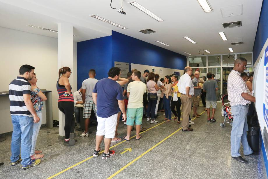 Pessoas formam filas nos caixas eletrônicos de agência da Caixa Econômica Federal, em São Paulo, para saque do FGTS