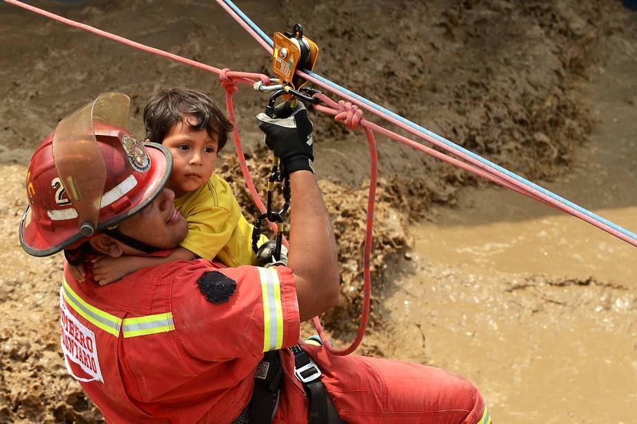 """Menino éajudado por um bombeiro após enchentes e deslizamentos na cidade de Huachipa. Os incidentes provocados pelo fenômeno climático<span>""""el niño costero""""</span> já mataram dezenas de pessoas no Peru - 17/03/2017"""