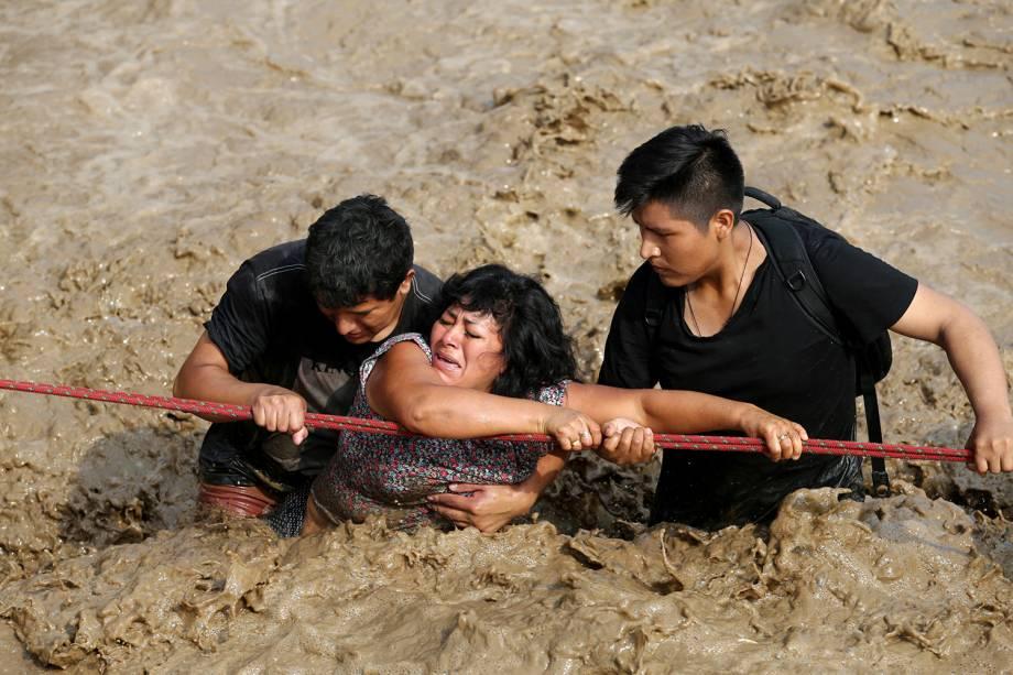 Mulher é auxiliada na travessia de uma rua após o rio Huaycoloro transbordar em Huachipa, no Peru - 17/03/2017