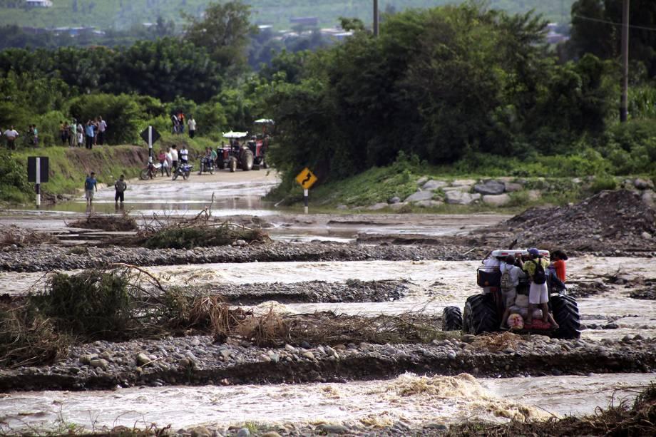 Na cidade de Chiclayo, moradores usam tratores para se locomover após as enchentes e deslizamentos - 19/03/2017