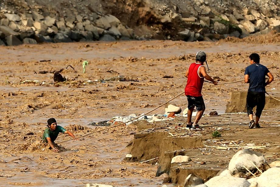Pessoas tentam atravessar o rio Rimac após transbordarmento no distrito de Huachipa, em Lima, Peru - 19/03/2017