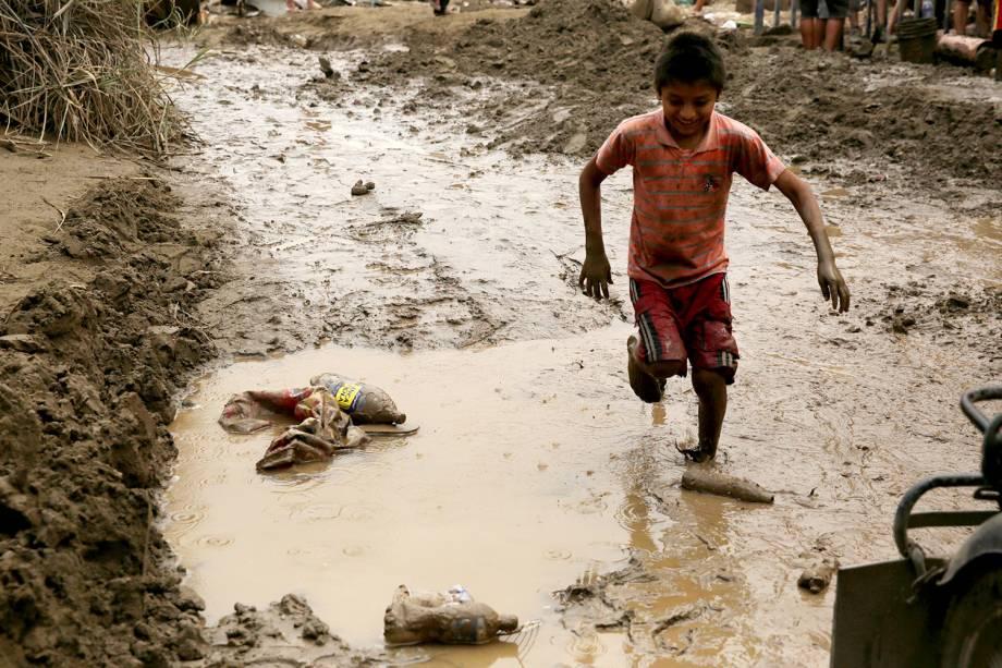 """Criança atravessa uma poça de lama emLima no Peru, após o fenômeno<span>""""el niño costero""""</span> causar enchentes e deslizamentos - 19/03/2017"""