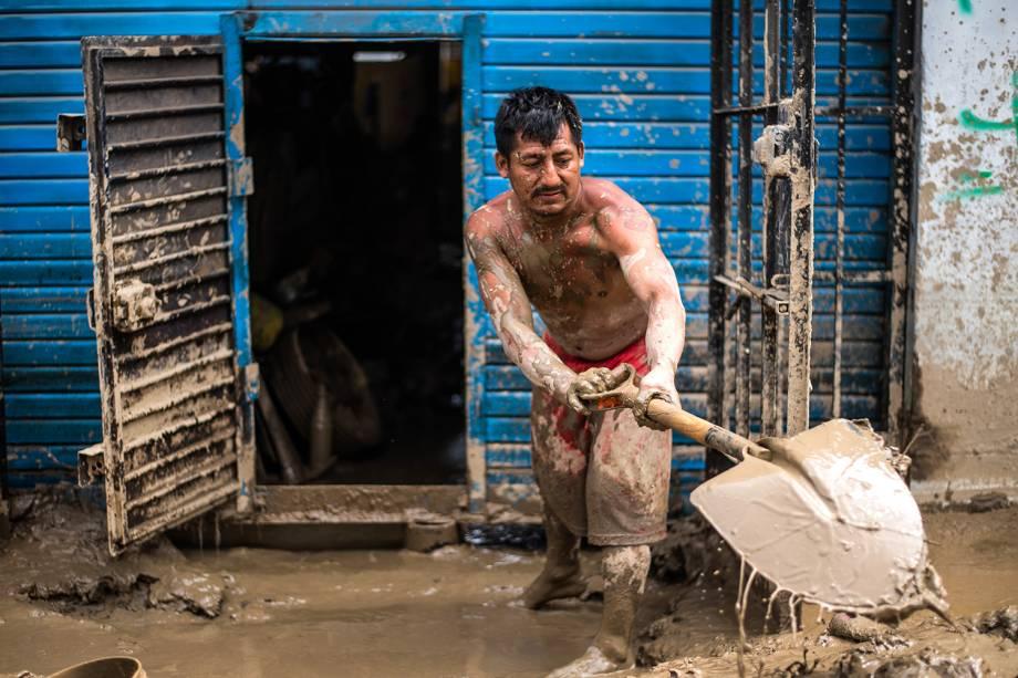 Morador de um distrito em Lima, Peru, remove lama de sua casa - 19/03/2017