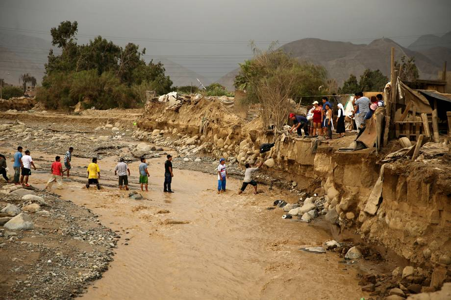 Voluntários entregam roupas às vítimas das enchentes no distrito de Cajamarquilla, Lima, Peru - 19/03/2017