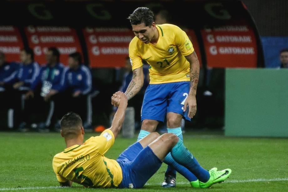Firmino ajuda Casemiro a se levantar após jogada dura com a defesa paraguaia