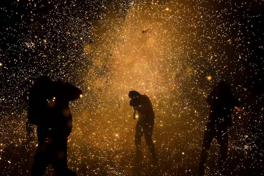 Pessoas protegem o rosto enquanto estouram fogos de artifício no festival do dia de San Juan de Diós, na Cidade do México