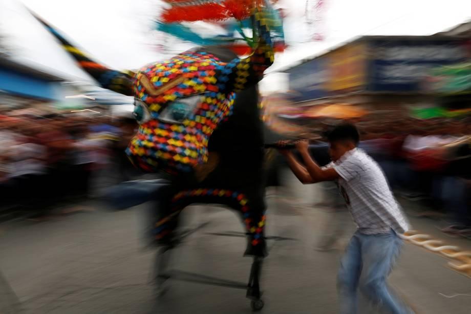 """Homem manuseia o """"Torito"""", boneco em formato de touro utilizado para armazenar os fogos do festival do dia de San Juan de Diós, na Cidade do México"""