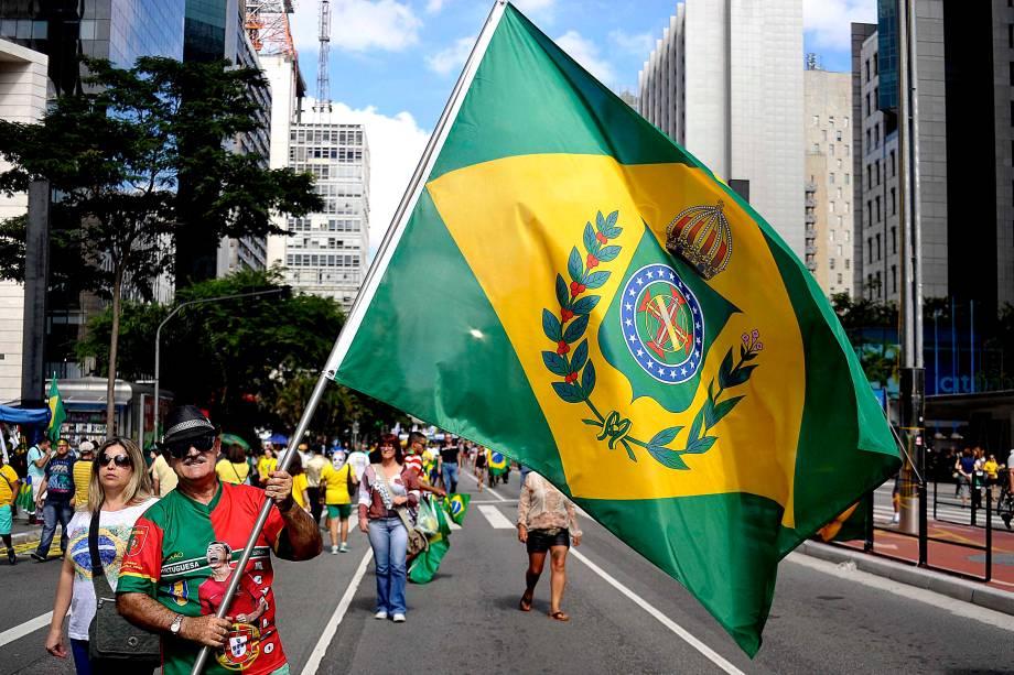 """Na Avenida Paulista, um manifestante levanta a bandeira da monarquia durante o protesto organizado pelos movimentos sociais MBL (Movimento Brasil Livre) e """"Vem Pra Rua"""", que também aconteceu em outras cidades do Brasil"""