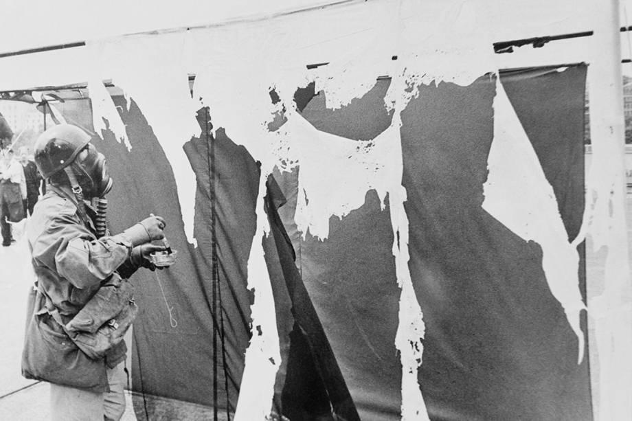 O artista alemão Gustav Metzger veste uma máscara de gás enquanto pinta cortinas de nylon com ácido clorídrico, fazendo com que se desintegram, em 1961