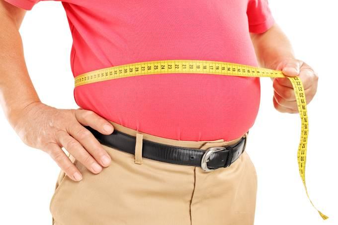 Homem gordo medindo a barriga com fica métrica