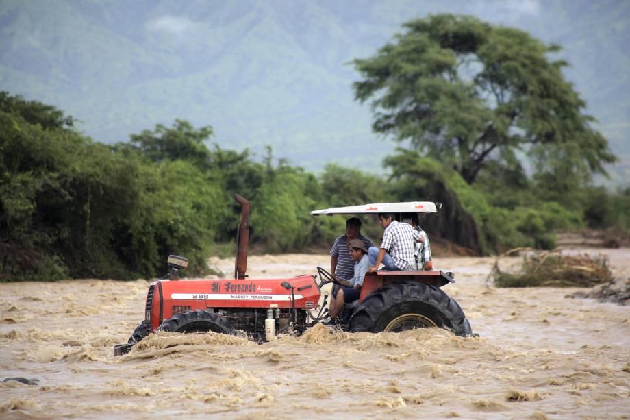 Camponeses usam um trator para atravessar as águas do Rio Zana nas proximidades da cidade de Chiclayo, ao norte de Lima no Peru. O fenômeno climático El Niño está causando o transbordamento de rios lamacentos ao longo de toda a costa peruana, isolando comunidades e bairros - 19/03/2017