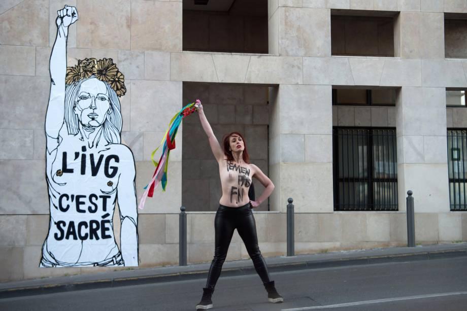 """Ativista é fotografada em frente a uma obra do artista francês Mahn com a inscrição """"IVG (Lei sobre o aborto voluntário) é sagrada"""" na Sede do Conselho Regional em Marselha, sul da França - 08/03/2017"""