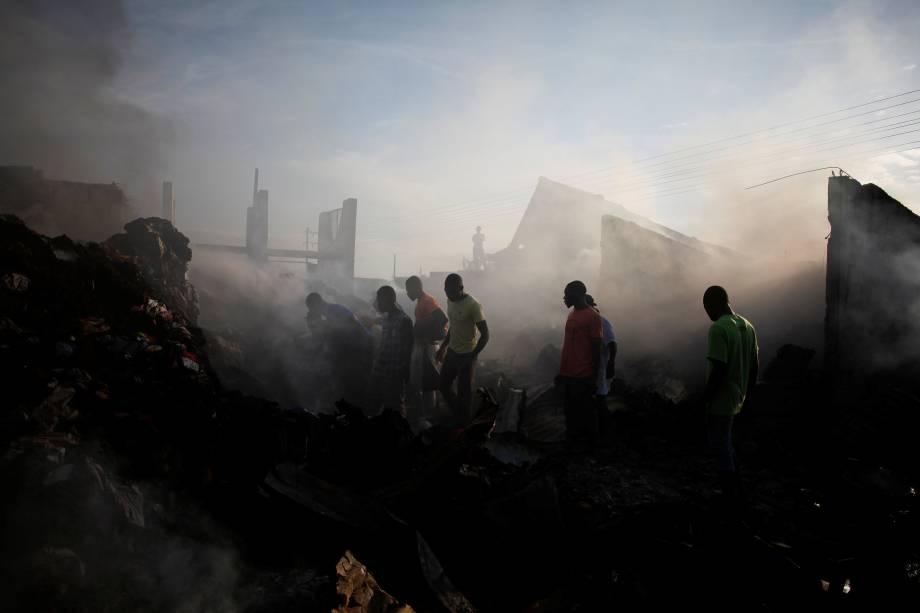 Pessoas procuram mercadorias nos escombros após um incêndio em um mercado de Porto Príncipe, no Haiti - 20/03/2017