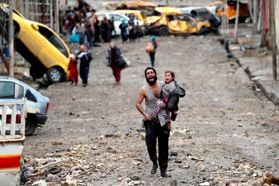 Pai carrega filha durante confronto entre o Estado Islâmico e as Forças Iraquianas em Mossul, Iraque - 06/03/2017