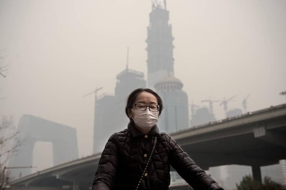 Mulher usa uma máscara protetora enquanto monta sua bicicleta em meio a um dia de intensa poluição em Pequim, na China - 20/03/2017